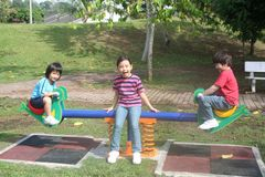 Kids at the playground. Happy kids enjoying seesaw at the playground in the park Stock Images