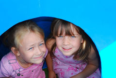 Kids on playground. Outdoor head portrait of two cute little Caucasian white girls with bright bue eyes and happy smiling expression in their faces sitting in a Stock Image