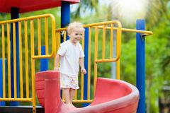 Kids on playground. Children play in summer park. Kids on climbing and sliding on outdoor playground. Children play in sunny summer park. Activity and amusement Royalty Free Stock Photography