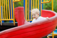 Kids on playground. Children play in summer park. Kids on climbing and sliding on outdoor playground. Children play in sunny summer park. Activity and amusement Royalty Free Stock Photos