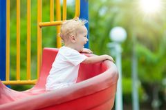 Kids on playground. Children play in summer park. Kids on climbing and sliding on outdoor playground. Children play in sunny summer park. Activity and amusement Royalty Free Stock Image