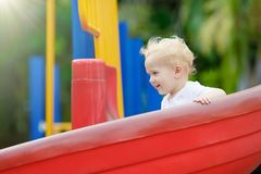 Kids on playground. Children play in summer park. Kids on climbing and sliding on outdoor playground. Children play in sunny summer park. Activity and amusement Royalty Free Stock Photo