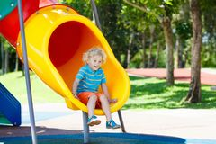 Kids on playground. Children play in summer park. Kids climbing and sliding on outdoor playground. Children play in sunny summer park. Activity and amusement Stock Photo