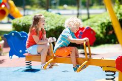 Kids on playground. Children play in summer park. Kids climbing and sliding on outdoor playground. Children play in sunny summer park. Activity and amusement Stock Photos