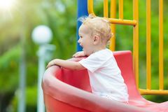 Kids on playground. Children play in summer park. Kids climbing and sliding on outdoor playground. Children play in sunny summer park. Activity and amusement Stock Images