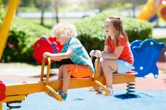 Kids on playground. Children play in summer park. Kids climbing and sliding on outdoor playground. Children play in sunny summer park. Activity and amusement Royalty Free Stock Photography