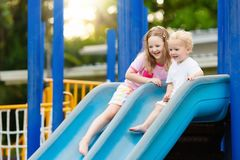 Kids on playground. Children play in summer park. Kids climbing and sliding on outdoor playground. Children play in sunny summer park. Activity and amusement Royalty Free Stock Photos
