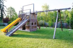 Kids playground in fenced back yard of house. Stock Image