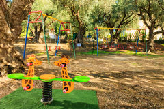 Kids playground in a garden. Modern kids playground in a beautiful garden with olive trees in a summer beach resort Royalty Free Stock Images