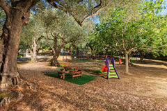 Kids playground in a garden. Modern kids playground in a beautiful garden with olive trees in a summer beach resort Stock Photography
