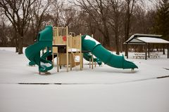 Kids playground and slides under a blanket of snow. Kids playground and slides under a blanket of fresh snow in winter in a rural park with bare deciduous trees Royalty Free Stock Photo