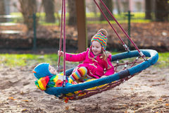 Kids on playground swing. Little boy and girl on a playground. Child playing outdoors in autumn. Kids play on school yard. Happy kid in kindergarten or preschool Royalty Free Stock Photos