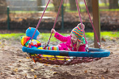 Kids on playground swing. Little boy and girl on a playground. Child playing outdoors in autumn. Kids play on school yard. Happy kid in kindergarten or preschool Stock Images