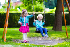 Kids on playground swing. Little boy and girl on a playground. Child playing outdoors in summer. Kids play on school yard. Happy kid in kindergarten or preschool Stock Photography