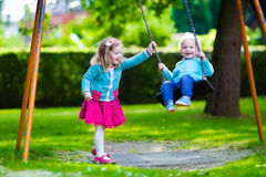 Kids on playground swing. Little boy and girl on a playground. Child playing outdoors in summer. Kids play on school yard. Happy kid in kindergarten or preschool Royalty Free Stock Image
