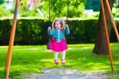 Kids on playground swing. Little boy and girl on a playground. Child playing outdoors in summer. Kids play on school yard. Happy kid in kindergarten or preschool Royalty Free Stock Photos