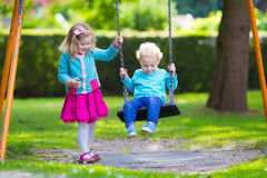 Kids on playground swing. Little boy and girl on a playground. Child playing outdoors in summer. Kids play on school yard. Happy kid in kindergarten or preschool Stock Photo