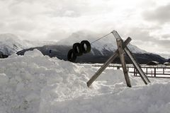 A kids playground under snow and snowy mountains and a small town in the alps switzerland.  Royalty Free Stock Image