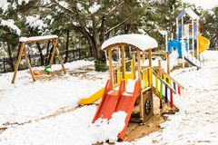 Kids playground in winter. Colorful kids playground caovered in snow in winter stock image