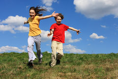 Kids playing. Kids running, jumping on green meadow stock photo