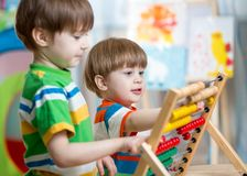 Kids playing with abacus. Happy kids brothers play with abacus toy at children room Stock Photography