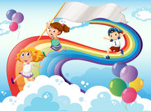Kids playing above the rainbow with an empty banner Royalty Free Stock Images
