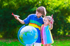 Kids playing with airplanes and globe in a garden Stock Images