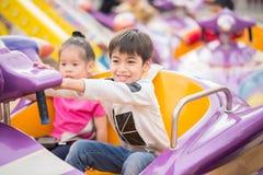 Kids playing in amusement fun park Stock Photos