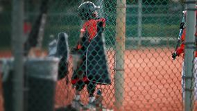 Kids playing around as they wait to bat at baseball game. Shot from behind a fence of two unrecognizable kids playing around on their uniforms before batting stock video footage