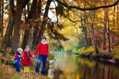 Kids playing in autumn park. Happy children playing on river shore in beautiful autumn park on warm sunny fall day. Kids play with golden maple leaves Stock Images