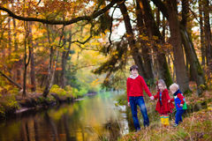 Kids playing in autumn park. Happy children playing on river shore in beautiful autumn park on warm sunny fall day. Kids play with golden maple leaves Royalty Free Stock Photo