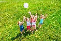Kids playing ball on a meadow. Five kids playing ball on a dandelion meadow Stock Photo