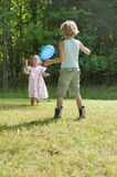 Kids playing with a balloon Stock Photos