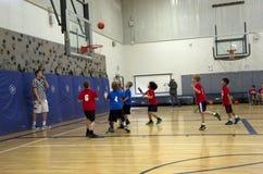 Kids playing basketball match stock photo