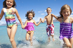 Kids playing at the Beach. A group of Happy Children running, playing and Splashing on a beach vacation together. Selective Focus on the two middle kids Stock Photography