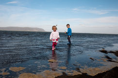 Kids playing on the beach. Photo of children playing on beach in Iceland Royalty Free Stock Image