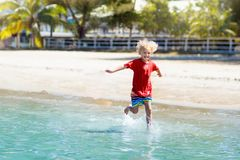 Kids playing on beach. Children play at sea. Kids playing on tropical beach. Children swim and play at sea on summer family vacation. Sand and water fun, sun stock photo