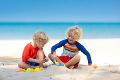 Kids playing on beach. Children play at sea. Kids playing on tropical beach. Children play at sea on summer family vacation. Sand and water toys, sun protection stock photography