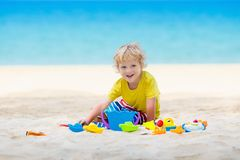 Kids playing on beach. Children play at sea. Kids playing on tropical beach. Children play at sea on summer family vacation. Sand and water toys, sun protection stock images