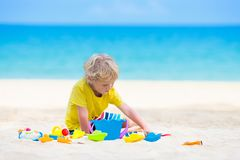 Kids playing on beach. Children play at sea. Kids playing on tropical beach. Children play at sea on summer family vacation. Sand and water toys, sun protection stock photo