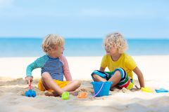 Kids playing on beach. Children play at sea. Kids playing on tropical beach. Children play at sea on summer family vacation. Sand and water toys, sun protection royalty free stock images