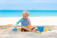 Kids playing on beach. Children play at sea. Kids playing on tropical beach. Children play at sea on summer family vacation. Sand and water toys, sun protection royalty free stock photo