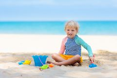 Kids playing on beach. Children play at sea. Kids playing on tropical beach. Children play at sea on summer family vacation. Sand and water toys, sun protection royalty free stock image