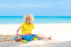 Kids playing on beach. Children play at sea. Kids playing on tropical beach. Children play at sea on summer family vacation. Sand and water toys, sun protection royalty free stock photos