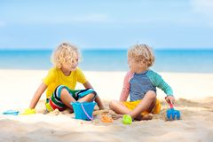 Kids playing on beach. Children play at sea. Kids playing on tropical beach. Children play at sea on summer family vacation. Sand and water toys, sun protection stock image