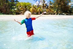 Kids playing on beach. Children play at sea. Kids playing on tropical beach. Children swim and play at sea on summer family vacation. Sand and water fun, sun stock images