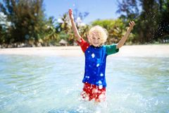 Kids playing on beach. Children play at sea. Kids playing on tropical beach. Children swim and play at sea on summer family vacation. Sand and water fun, sun royalty free stock photography