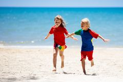 Kids playing on beach. Children play at sea. Kids playing on tropical beach. Children swim and play at sea on summer family vacation. Sand and water fun, sun stock photos