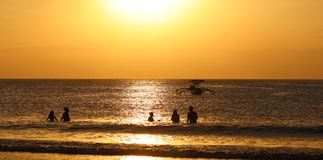 Kids playing at the beach with fisherman boat in Bali, Indonesia during sunset at the beach. stock photo