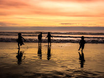 Kids playing on beach. At sunset in summer Stock Photos